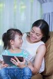 Mère et fille à l'aide de la Tablette de Digital Famille passant le temps t Images stock