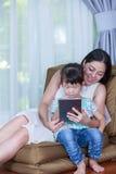 Mère et fille à l'aide de la Tablette de Digital Famille passant le temps t Photographie stock libre de droits