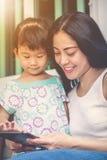Mère et fille à l'aide de la Tablette de Digital Famille passant le temps t Image stock