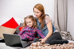Mère et fille à l'aide de l'ordinateur portable sur le lit dans la chambre à coucher La mère étreint sa fille avec l'amour et soi images stock