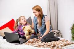Mère et fille à l'aide de l'ordinateur portable sur le lit dans la chambre à coucher Ils regardent l'affichage et le rire photos stock