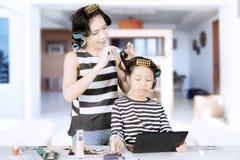 Mère et fille à l'aide des rouleaux à la maison Photographie stock