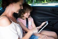 Mère et fille à l'aide du comprimé numérique dans la voiture Photo libre de droits