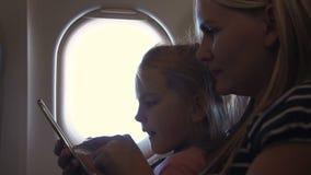 Mère et fille à l'aide du smartphone dans l'avion clips vidéos