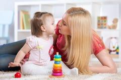 Mère et fille à l'intérieur jouant et souriant Images stock