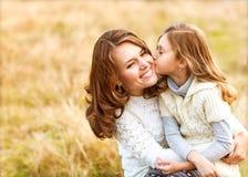 Mère et fille étreignant dans l'amour jouant en parc Image stock