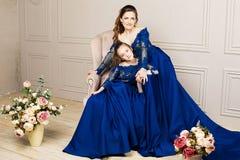 Mère et fille étreignant et regardant l'appareil-photo Famille affectueuse heureuse Mère et fille dans de beaux longs dres bleus  Images stock