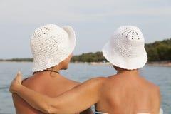 Mère et fille étreignant sur le bord de mer, plage ensoleillée Image stock