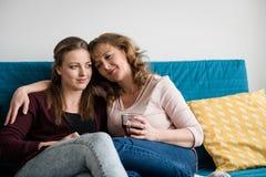 Mère et fille adolescente étreignant sur le sofa à la maison Photographie stock libre de droits