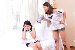 Mère et fille adolescente parlant dans le salon photo stock