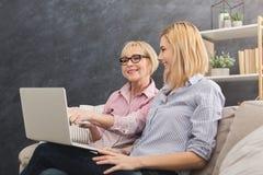 Mère et fille adultes heureuses à l'aide de l'ordinateur portable à la maison Photos libres de droits