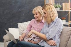 Mère et fille adultes heureuses à l'aide de l'ordinateur portable à la maison Photo stock