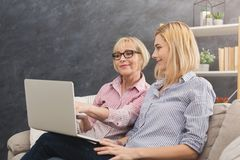 Mère et fille adultes heureuses à l'aide de l'ordinateur portable à la maison Photos stock