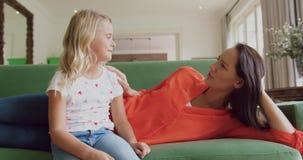 Mère et fille agissant l'un sur l'autre les uns avec les autres sur le sofa à la maison 4k banque de vidéos