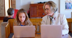 Mère et fille agissant l'un sur l'autre les uns avec les autres tout en à l'aide de l'ordinateur portable 4k clips vidéos