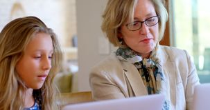 Mère et fille agissant l'un sur l'autre les uns avec les autres tout en à l'aide de l'ordinateur portable 4k banque de vidéos