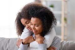 Mère et fille aimantes avec l'embrassement fermé de yeux images libres de droits