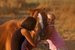 Mère et fille alimentant son cheval beau Image stock