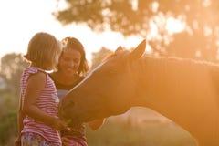 Mère et fille alimentant son cheval beau Images stock