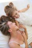 Mère et fille appréciant et jouant dans le lit Photographie stock