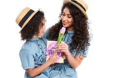 mère et fille avec la carte de voeux et la fleur de jour de mères Photographie stock