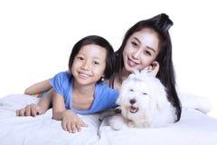 Mère et fille avec le chiot sur le studio Photos stock