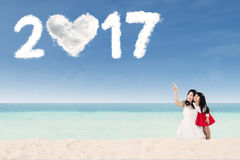 Mère et fille avec le numéro 2017 sur la plage Photo stock