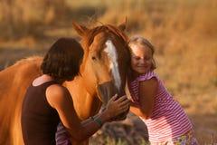 Mère et fille avec leur cheval beau Photographie stock