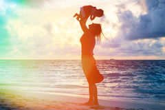 Mère et fille ayant l'amusement à la plage de coucher du soleil Photos stock