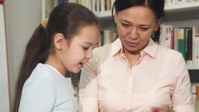 Mère et fille choisissant des livres à la bibliothèque ou à la librairie banque de vidéos