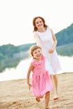 Mère et fille courant au-dessus de la plage Photo stock