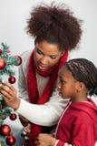 Mère et fille décorant l'arbre de Noël Photographie stock