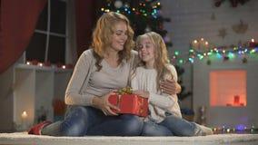 Mère et fille déformant Noël actuel pour le papa et étreignant, préparations clips vidéos