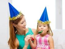 Mère et fille dans des chapeaux bleus avec des klaxons de faveur image stock