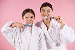 Mère et fille dans des dents de brosses de robes Photos libres de droits