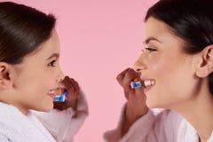 Mère et fille dans des dents de brosses de robes Image stock