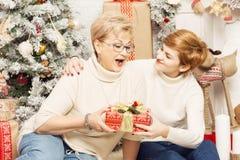 Mère et fille dans le ` s de nouvelle année intérieur, donnant des cadeaux photos libres de droits