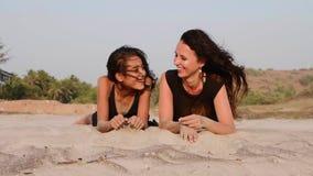 Mère et fille de l'adolescence se trouvant ensemble sur la plage sablonneuse, parler et rire banque de vidéos