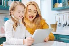 Mère et fille de sourire à l'aide d'un comprimé Photo stock