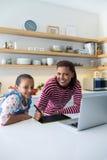 Mère et fille de sourire à l'aide du comprimé graphique dans la cuisine Photo libre de droits