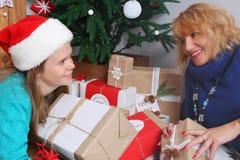 Mère et fille de sourire avec des décorations et des cadeaux de Noël Photographie stock libre de droits