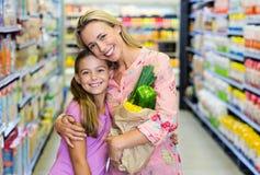 Mère et fille de sourire avec le sac d'épicerie images libres de droits