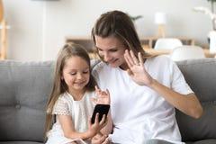 Mère et fille de sourire faisant l'appel visuel sur le smartphone images stock