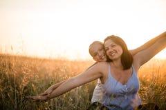 Mère et fille de sourire insouciantes dans le domaine au coucher du soleil photo libre de droits