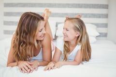Mère et fille de sourire se trouvant sur le lit Images libres de droits