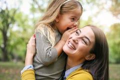 Mère et fille dehors dans un pré Fille chuchotant à Image stock
