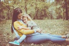 Mère et fille dehors dans un pré Petite fille s'asseyant dessus Image stock
