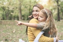 Mère et fille dehors dans un pré Petite fille s'asseyant dessus Photo libre de droits