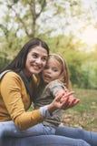 Mère et fille dehors dans un pré Petite fille s'asseyant dessus Photographie stock libre de droits