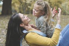 Mère et fille dehors dans un pré Petite fille s'asseyant dessus Photos stock
